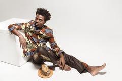 传统衣裳的想知道的非洲的人坐coub 免版税库存图片