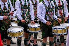 传统衣裳的鼓手穿过城市拉扯鼓 库存图片