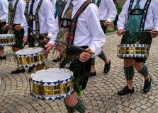 传统衣裳的鼓手穿过城市拉扯鼓 图库摄影