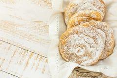 传统西班牙或菲律宾酥皮点心ensaimada 搽粉在柳条筐 白色木桌 舒适土气厨房内部 免版税库存照片
