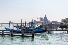 传统长平底船美丽的景色在运河的重创与大教堂二圣玛丽亚della致敬在威尼斯,意大利 免版税库存图片