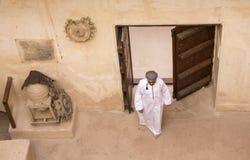 传统阿曼成套装备的阿拉伯人在一座老城堡 图库摄影
