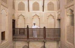 传统阿曼成套装备的阿拉伯人在一座老城堡 库存照片