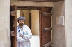 传统阿曼成套装备的阿拉伯人在一座老城堡 免版税库存图片