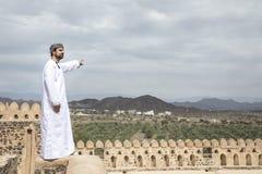传统阿曼成套装备的阿拉伯人指向距离的 图库摄影