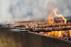 传统阿达纳kebab在有桔黄色火焰的bbq烤了并且抽烟,关闭,室外 库存照片