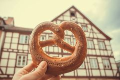 传统面包椒盐脆饼在手中人过去老房子在德国 历史城市和甜酥皮点心的巴法力亚家 库存照片