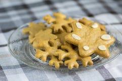 传统鲜美捷克姜饼、圣诞节雪花和星在玻璃板在灰色方格的桌布 免版税库存图片