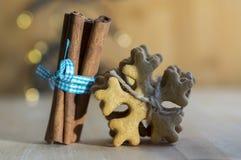 传统鲜美捷克姜饼栓与黄麻系住,与蓝色弓、圣诞节雪花和香料的新鲜的桂香在木 免版税库存图片