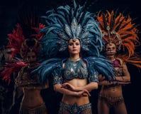 传统brasilian carnaval服装的三美女为摄影师摆在演播室 库存照片