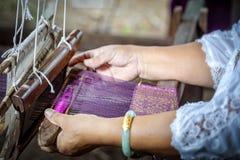 传统Isan泰国丝绸编织 老妇人手编织的丝绸用在手工织布机的传统方式 ?? r 免版税图库摄影