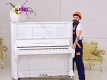 传讯者交付家具,搬出,拆迁 装载者移动钢琴仪器 有胡子工作者的人盔甲的和 免版税库存照片