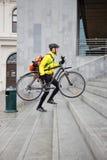 传讯者有自行车和背包的送货人 免版税库存照片