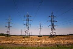 传输塔和输电线行在领域 免版税库存图片