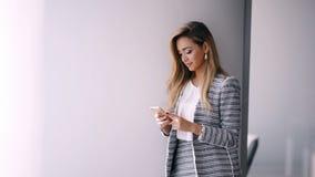 传送与智能手机的女实业家信息在办公室 影视素材