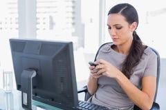 传送信息的可爱的深色头发的女实业家 免版税库存照片