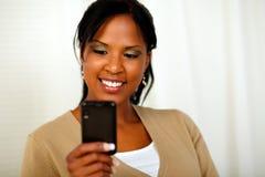 传送信息的迷人的黑人妇女由移动电话 免版税库存照片