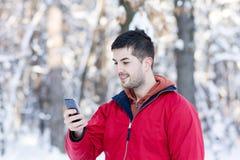 传送信息的年轻人画象在冬天森林里 免版税库存图片