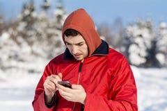 传送信息的年轻人画象在冬天森林里 免版税库存照片