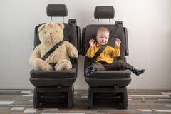 传送带驱动安全性位子票的汽车单击 一个愉快的孩子在自动扶手椅子坐在玩具熊旁边 公路安全的概念 图库摄影