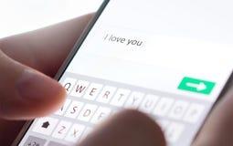 传送我爱你与手机的短信 在网上约会,短信或者catfishing概念 拉丁文的欺骗,诈欺 免版税库存照片