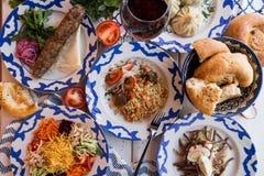 传统乌兹别克人晚餐 肉饭,女用披巾, kebab,在桌上的面包与菜 免版税图库摄影