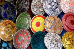 传统五颜六色的摩洛哥精巧彩色陶器瓦器盘在马拉喀什,摩洛哥麦地那的souk的一家典型的古老商店  免版税图库摄影