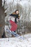传统俄国服装的俄国妇女做的滑稽的障碍滑雪 库存照片