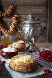 传统俄国薄煎饼用酸奶干酪、牛奶、百吉卷和俄国式茶炊 库存照片