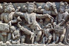 传统印地安衣裳的滑稽的跳舞人民 12世纪印度寺庙Hoysaleshwara安心在Halebidu,印度 免版税库存照片