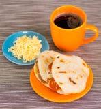传统可口arepas、切细的鸡鲕梨和切达干酪和切细的牛肉与一个杯子coffe与 免版税库存图片