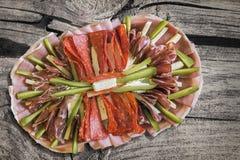 传统塞尔维亚在被风化的老破裂的木野餐桌上的开胃菜美味盘集合 免版税库存照片