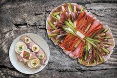 传统塞尔维亚开胃菜美味盘用老野餐桌难看的东西表面上设置的食家烟肉和鸡蛋三明治 免版税库存照片