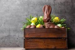 传统复活节巧克力兔宝宝和鸡蛋在一个木板箱里面 图库摄影