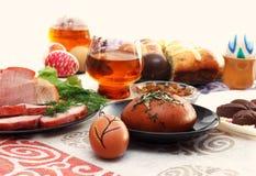 传统复活节餐具用切的肉、面包用草本,手工制造色的鸡蛋、巧克力、复活节ju蛋糕和玻璃  免版税库存图片