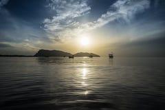 传统小船在海的波浪表面放置有一朵长的大山、美好的日出和云彩的在一个早晨 免版税库存图片