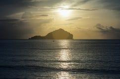 传统小船在海的波浪表面放置有一朵长的大山的、美好的日出或者日落和云彩,被过滤 免版税图库摄影