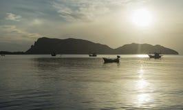 传统小船在海的波浪表面有一座长的大山的,日出放置在一个早晨,泰国 库存照片