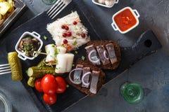 传统快餐盐溶了与菜、葱、猪油、面包、土豆和伏特加酒两射击的鲱鱼  免版税图库摄影