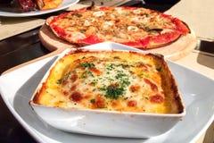 传统意大利烤宽面条做用剁碎的牛肉博洛涅塞调味汁冠上与蓬蒿叶子在一块白色板材服务 免版税库存照片