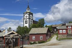 传统房子和教堂钟Roros,挪威铜矿镇的塔外部  库存图片