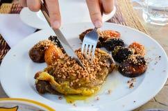 传统摩洛哥盘羊羔tagine用干果子:无花果、杏子、修剪、杏仁和芝麻籽 库存照片