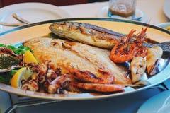 传统斯洛文尼亚烹调、混杂的烤鱼和海鲜用大蒜油 选择聚焦 库存图片