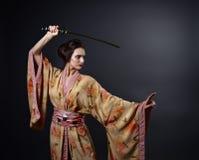 传统日本和服的美丽的妇女有katana的 免版税库存图片