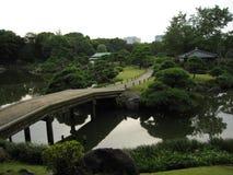 传统日语漫步有桥梁的庭院横跨池塘 免版税库存照片
