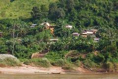 传统木村庄和渔船在湄公河在老挝 免版税库存图片