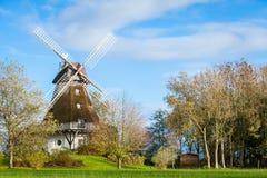 传统木风车在一个繁茂花园里 免版税图库摄影
