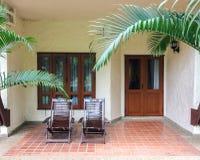 传统木轻便折叠躺椅夫妇在阳台露台或大阳台在开阔地带在Windows前面和门的为放松 免版税图库摄影