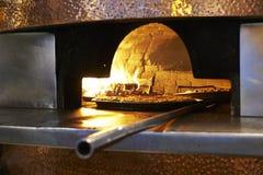 传统木头射击了被安置入一块超级热的砖的薄饼 免版税库存图片