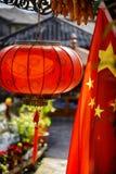 传统朱红色的灯笼和中国的旗子 免版税库存照片